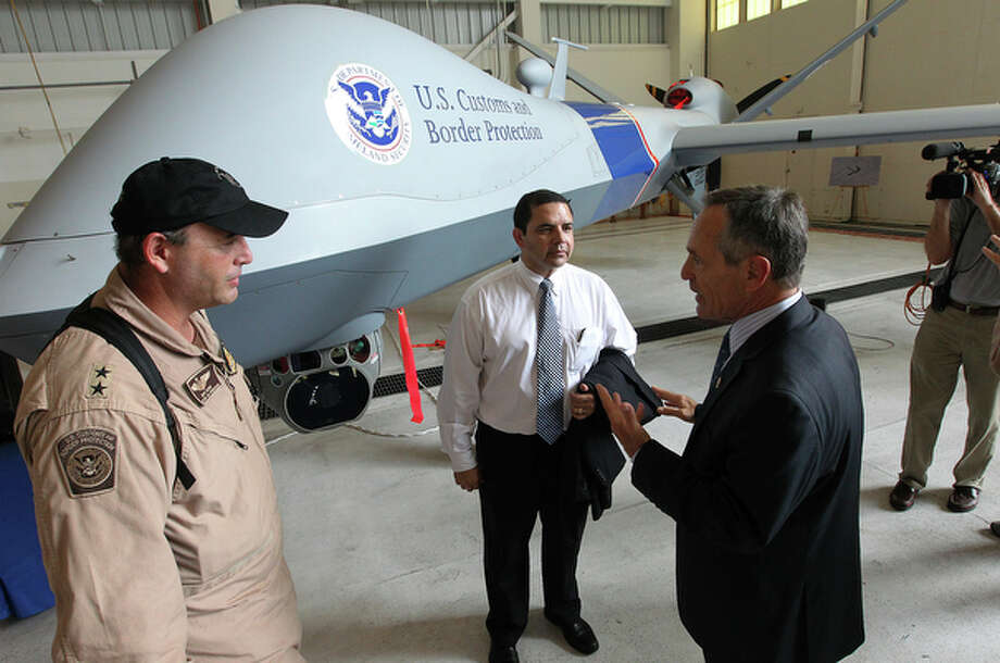 Rep. Henry Cuellar (center), D-Laredo, along with U.S. Customs and Border Protection Commissioner Alan Bersin (right) and Director of Operations for the Sierra Vista, Arizona office David Gasho (left) chat in front of the MQ-9, Predator B unmanned aircraft. / San Antonio Express-News