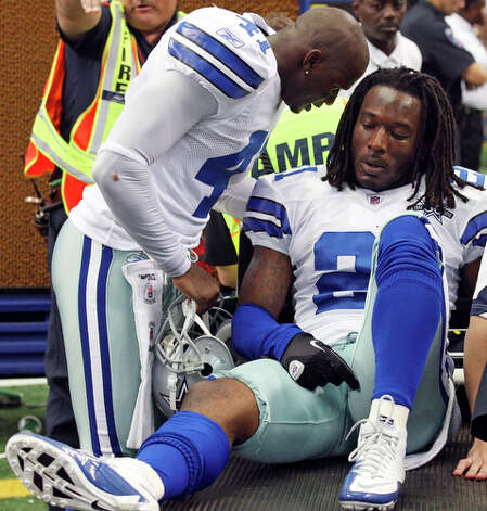 Cowboys' Terence Newman (left) talks with teammate Cowboys' Mike Jenkins as he is taken off the field after an injury. / eaornelas@express-news.net