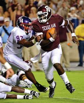 Texas  A&M quarterback Jerrod Johnson (right) tries to pull away from Stephen F. Austin's Kenneth Charles.