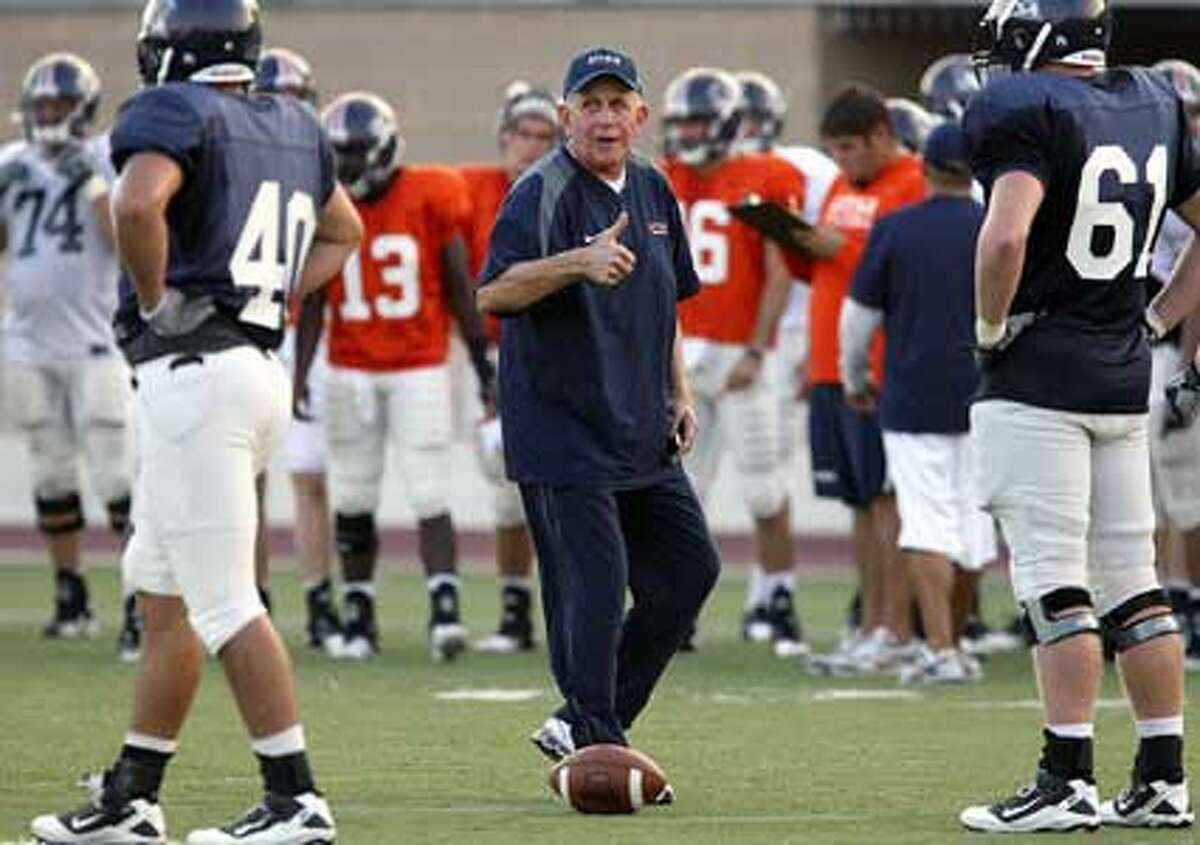 UTSA football coach Larry Coker (center) gives the thumbs-up to defensive players during his team?s first scrimmage, at Farris Stadium on Wednesday. The Roadrunners are attempting to get a thumbs-up for entry into the WAC.