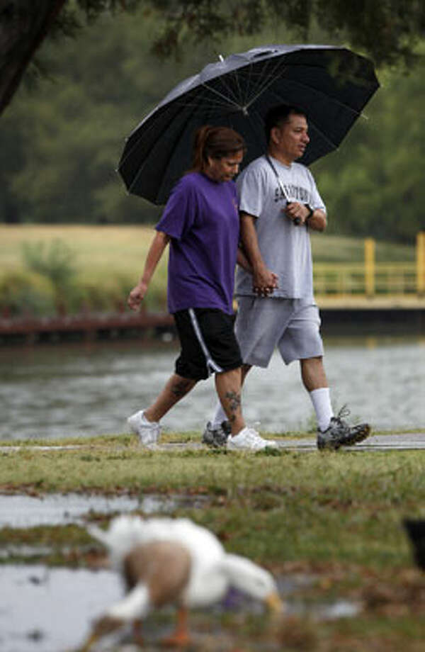 Sandra Riggins and Ben Juarez walk in the rain around Woodlawn Lake as ducks eat bugs in nearby puddles of water. San Antonio received nearly 1.5 inches of rain Friday morning.