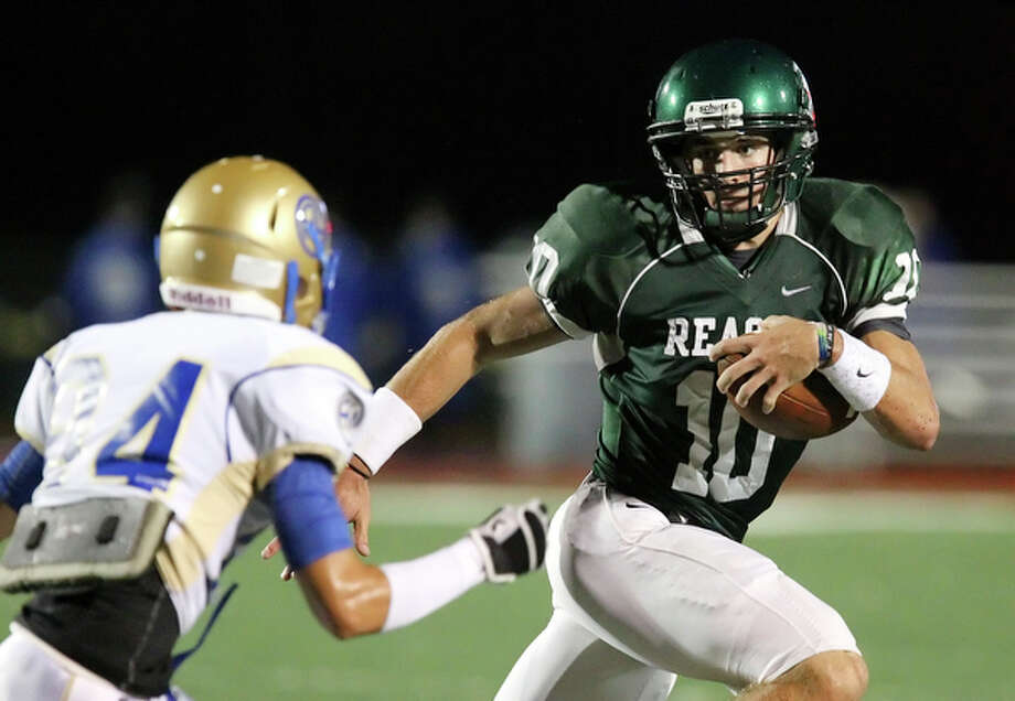 Reagan quarterback Trevor Knight (10) evades Alamo Heights' Garret Hisle (84). / San Antonio Express-News