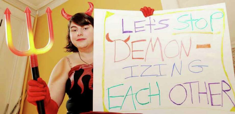 "Shannon Barton, wearing her ""Little Devil"" costume with her ""Stop demonizing each other"" sign at her home in Troy, NY, on Thursday, Oct. 28, 2010, as she prepares for her trip to Washington, D.C., for Saturday's ""Rally To Restore Sanity.""   (Luanne M. Ferris / Times Union ) Photo: Luanne M. Ferris"