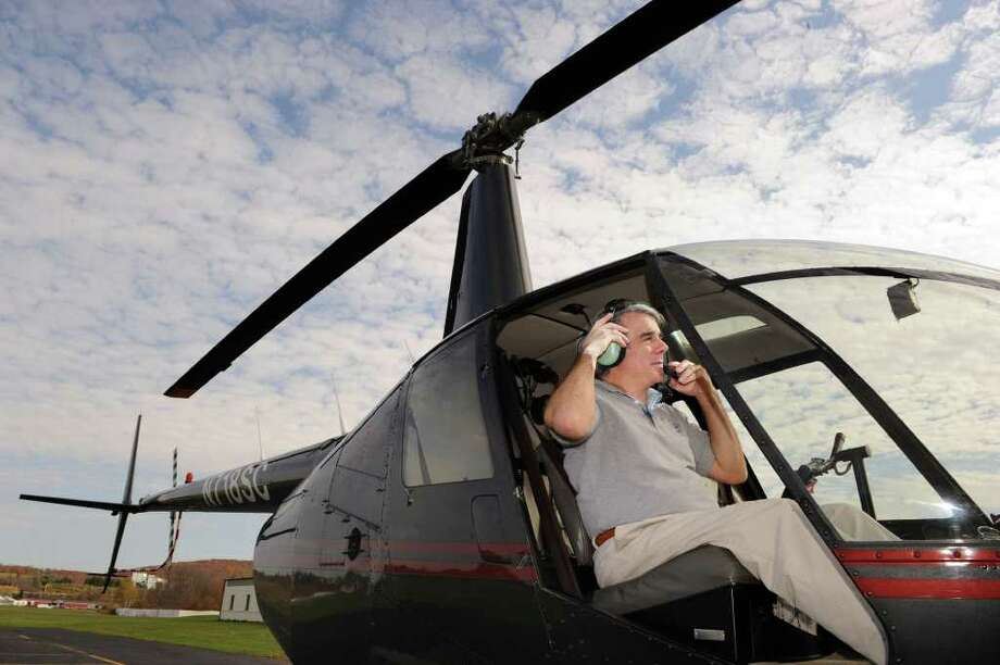 Michael DeMarchi, general manager and lead pilot for Centennial Helicopters in Danbury, sits in the cockpit of a Robinson R44 helicopter at the company's headquaters in Danbury. Photo taken Thursday, Oct. 28, 2010. Photo: Carol Kaliff / The News-Times