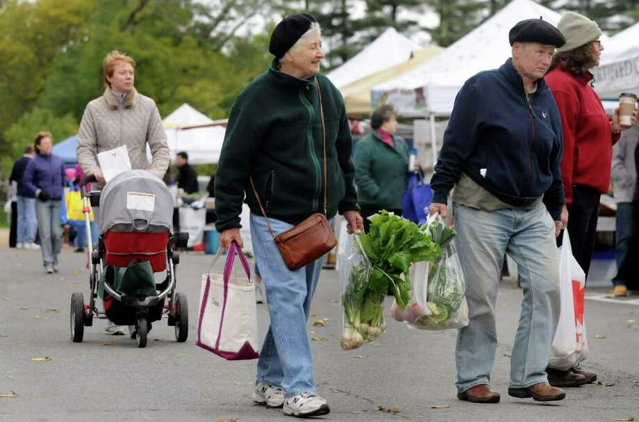 Sara McCain of Delman, center, and Judith Fetterley of Glenmont, right, leave with their goods at the Delmar Farmers Market on Saturday, Oct. 16, 2010, at Bethlehem Central Middle School in Delmar, N.Y. (Cindy Schultz / Times Union) Photo: Cindy Schultz