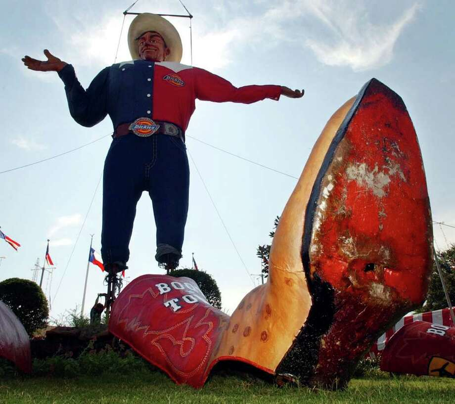 """State Fair of Texas icon """"Big Tex,""""  hangs from a crane as workers at the base of the structure mount it to the ground, Monday, Sept. 22, 2003, in Dallas. """"Big Tex"""" is a 52-foot structure that speaks, greeting fair-goers to the fair ground for the Texas State Fair that begins Sept 26 and runs through Oct. 19. (AP Photo/Tony Gutierrez) / AP2003"""