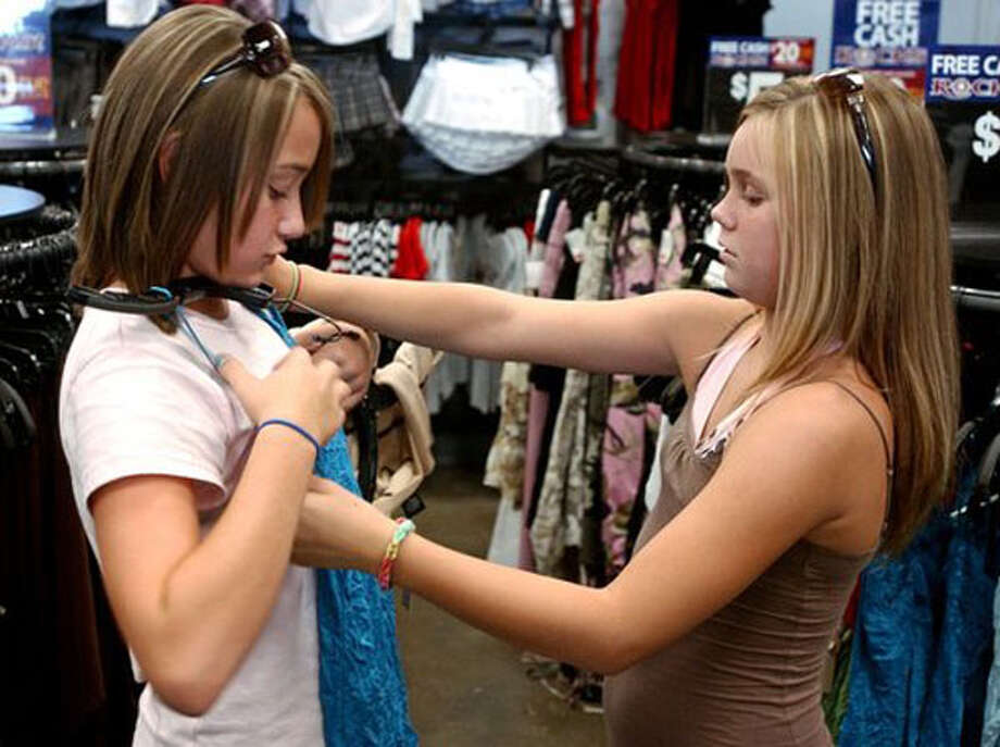 Zara Killman, 11, left, gets help selecting clothes from her best friend Avery Foret, 11, at Rue 21 in Beaumont during the sales tax free shopping holiday in August. 2006. Enterprise file photo / Beaumont