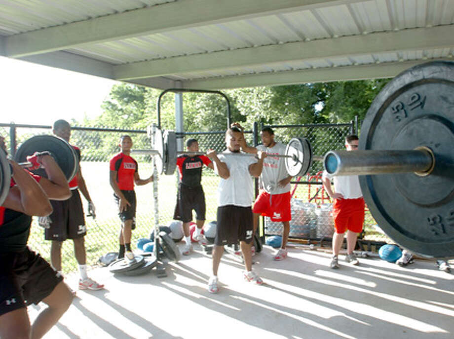 Lamar University football players work out in the weightlifting area of the their practice field early Monday morning. Pete Churton/The Enterprise / Beaumont