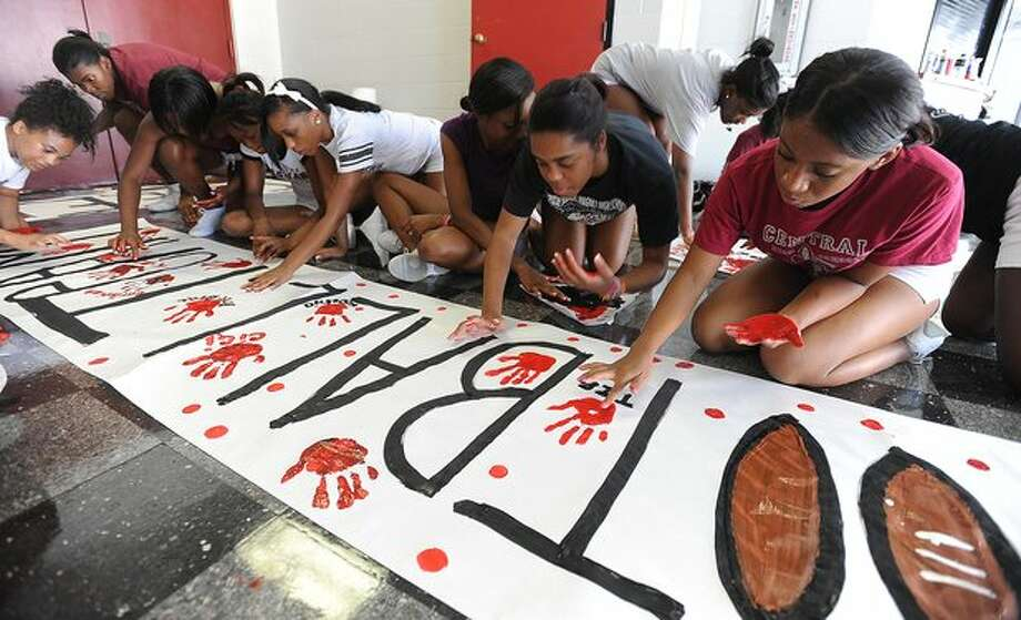 In preparation for this weekends game, Central's cheerleaders paint banners at school Wednesday to boost school spirit. Guiseppe Barranco/The Enterprise / Beaumont