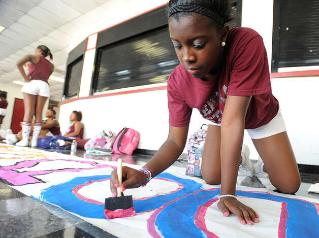 Lauren Miller paints a banner at Central High School on Wednesday in preparation for Friday's game. Guiseppe Barranco/The Enterprise / Beaumont