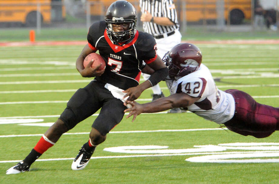 Memorial's Terrence Singleton runs the ball as Central's Terrance Watts reaches for the tackle at the Memorial High School stadium in Port Arthur, Friday. Tammy McKinley/The Enterprise / Beaumont