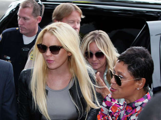 Lindsay Lohan, left, and attorney Shawn Chapman Holley arrive at the Beverly Hills courthouse in Beverly Hills, Calif., on Tuesday. Lohan was sentenced to 90 days in jail for a probation violation. AP Photo/Nick Ut / AP