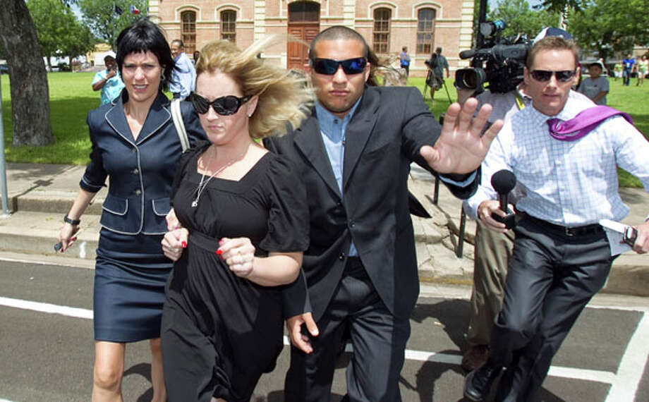 Nikki Araguz, front in sunglasses, is hurried across the street from the Wharton County Courthouse for a break during her temporary restraining order hearing  Friday in Wharton. Nick de la Torre/Chronicle / © 2010 Houston Chronicle