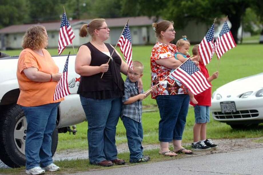 "Sour Lake residents watch as the Patriot Guard Riders lead a procession route to a memorial service honoring  Sgt. Leston ""Tony"" M. Winters, 30, of Sour Lake, Texas. Winters died July 15 in Kandahar, Afghanistan, of wounds sustained when enemy forces attacked his unit with an improvised explosive device.  Valentino Mauricio/The Enterprise / Beaumont"