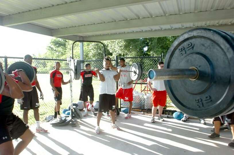 Lamar University football players work out in the weightlifting area of the their practice field. Pe