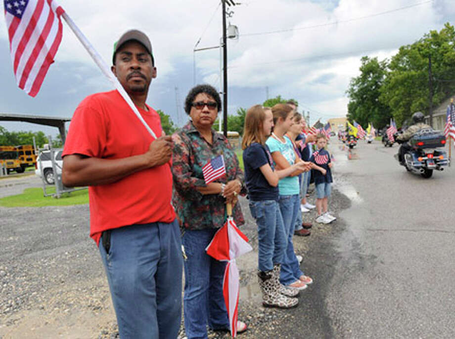"Bennett Fontenot, left, and Mary Alice Jones, center, along with hundreds of Sour Lake residents watch as the Patriot Guard Riders lead a procession route to a memorial service honoring Sgt. Leston ""Tony"" M. Winters, 30, of Sour Lake. Winters died July 15 in Kandahar, Afghanistan, of wounds sustained when enemy forces attacked his unit with an improvised explosive device. Valentino Mauricio/The Enterprise"