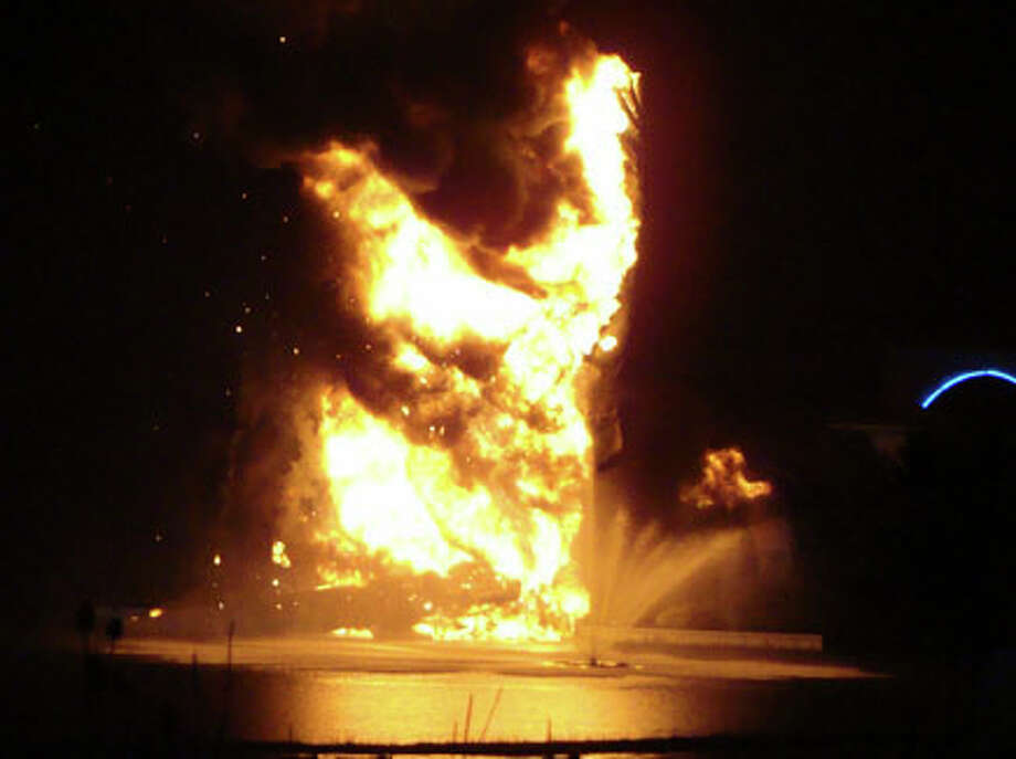 """Flames shoot up from the """"King of Kings"""" statue of Jesus Christ standing outside of Solid Rock Church in Monroe, Ohio, early Tuesday. The six-story-tall statue of Jesus with his arms raised along a highway was struck by lightning in a thunderstorm Monday about 11:15 p.m. and burned to the ground, police said. AP Photo/The Dayton Daily News, Tiffani West-May / The Dayton Daily News"""
