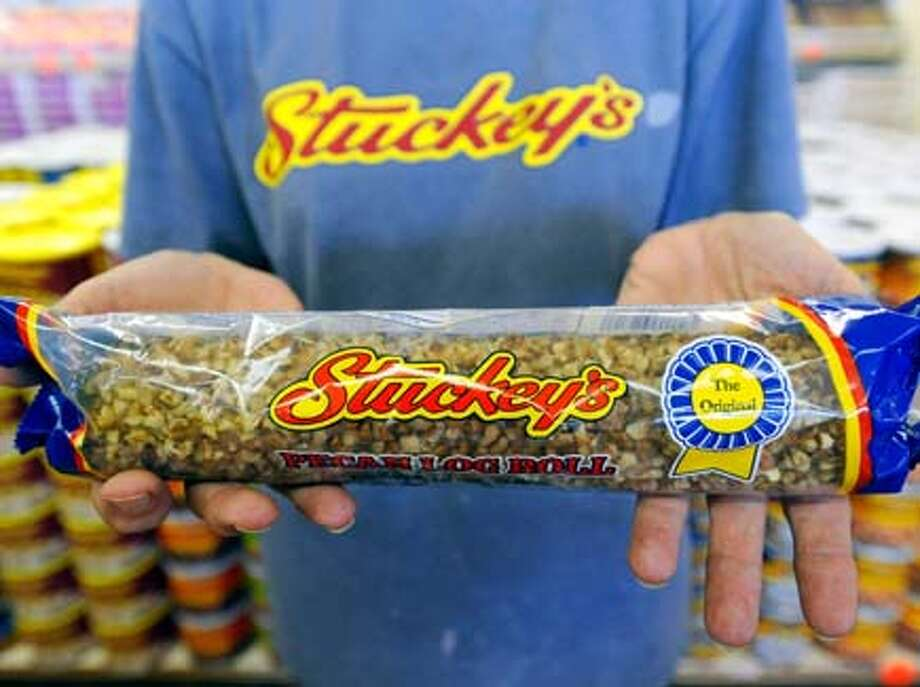 Stuckey's manager Chris Scott displays the ever popular 12 oz Pecan Log Roll at their store on Interstate 10 near Anahuac. Stuckey's, which is still popular and a holdover from the 1950s-'60s, has everything for the traveler's needs, from gasoline, pecan rolls, and kitschy souvenirs. Wednesday, August 4, 2010.  Valentino Mauricio/The Enterprise / Beaumont