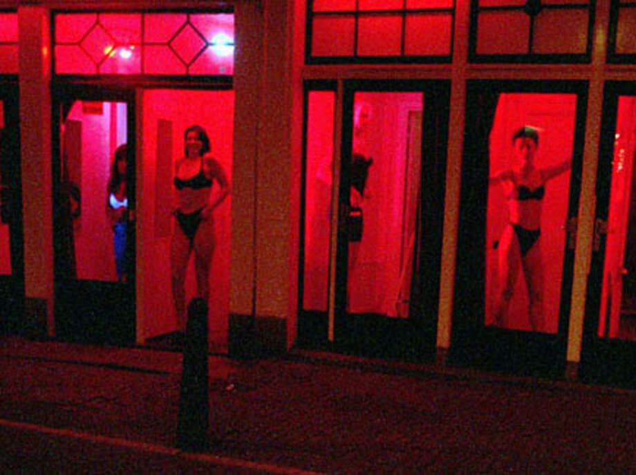 Girls stand in red-lit windows in Amsterdam's red light district. AP Photo/Peter Dejong / AP