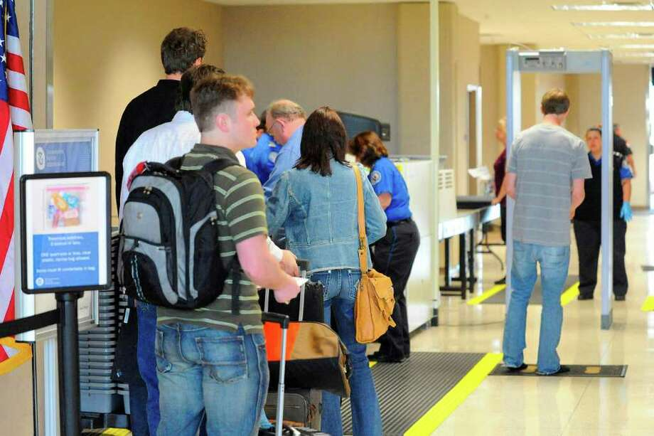 Passengers on their way to Houston go through the TSA security checkpoint Thursday at Southeast Texas Regional Airport before boarding their afternoon flight. Valentino Mauricio/The Enterprise / Beaumont