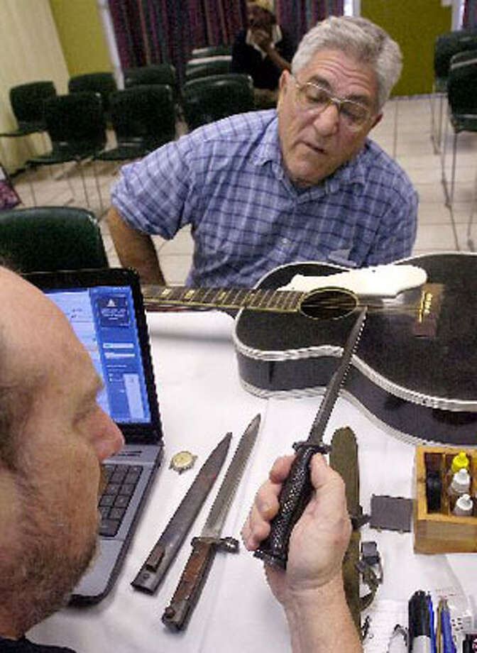 The Great Treasure Hunt is in Beaumont through Friday. John Sigona watches as Vince Pitti, left, an appraiser, examines World War I and World War II bayonets that he had brought in with his Harmony Jamboree guitar and old Lions Club pins.  Dave Ryan/The Enterprise