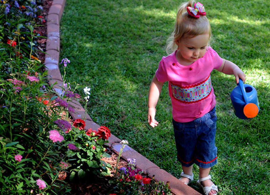 Tara Peters waters the flower garden in front of her grandmother's home in Village Mills, Wednesday. A photo of Tara is featured on a Mother's Day Hallmark card. Tammy McKinley/The Enterprise / Beaumont