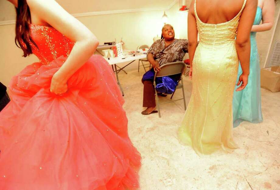 Roxane May assists foster girls with alterations of their prom gowns during the Prom Project event that allows foster children to receive clothes and accessories for proms and experience a mock prom Saturday at The Courtyard in Groves.  Tammy McKinley/ The Enterprise / Beaumont