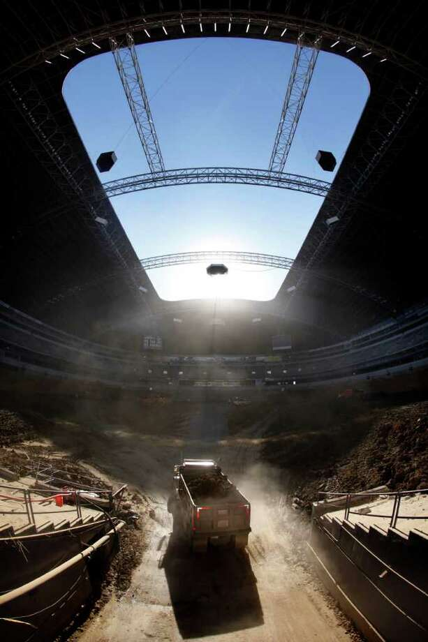 Dump trucks full of dirt are hauled into the arena floor after the lower bowl concrete seating was removed from Texas Stadium in Irving. The stadium is set to be demolished April 11. Tom Fox/The Associated Press / THE DALLAS MORNING NEWS