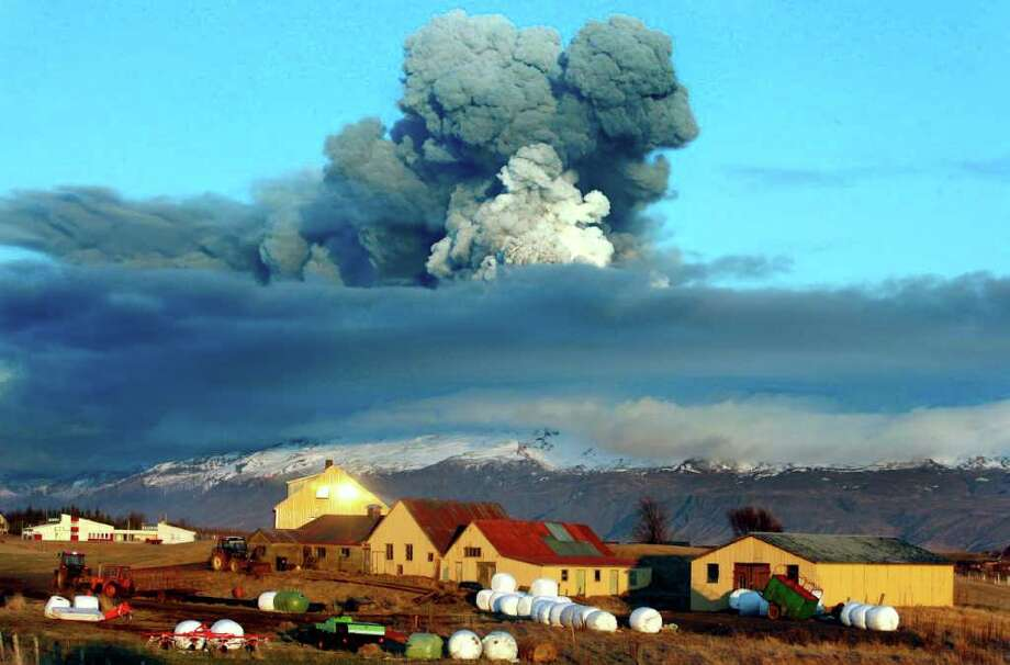 The volcano in southern Iceland's Eyjafjallajokull glacier sends ash into the air before sunset Friday. Thick drifts of volcanic ash blanketed parts of rural Iceland as a vast, invisible plume of grit drifted above Europe, emptying the skies of planes and sending hundreds of thousands in search of hotel rooms, train tickets or rental cars. Brynjar Gauti/The Associated Press