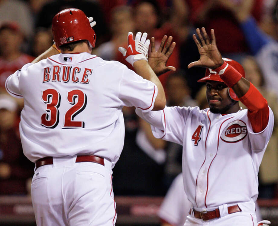Cincinnati Reds' Jay Bruce (32) is congratulated by Brandon Phillips (4) after Bruce hit a two-run home run off Los Angeles Dodgers starting pitcher Vicente Padilla in the sixth inning of a baseball game April 22 in Cincinnati. Cincinnati won the game 8-5. (AP Photo/Al Behrman) / AP