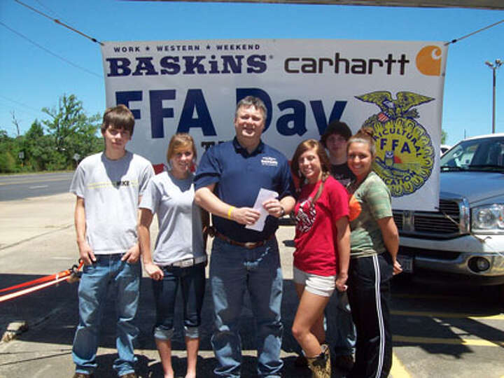 Baskings store manager, Scott Burton, presents a donation to the Kirbyville FFA Chapter.