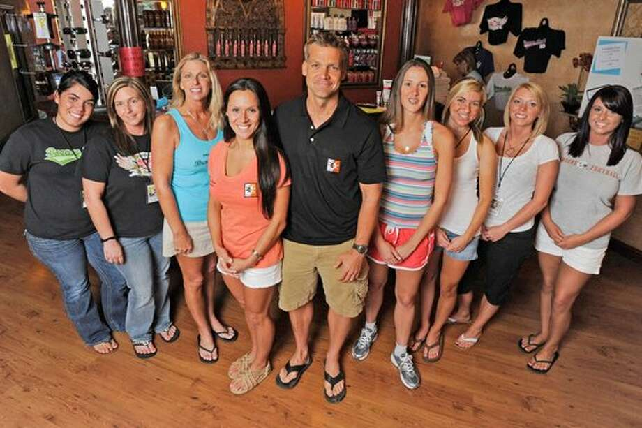 Bronze Body Tan owner Charlie Dixon, center, pictured at his Beaumont business along with a few of the  33  employees who will be running  and volunteering at the Gusher Marathon in Beaumont on Saturday. Valentino Mauricio/The Enterprise / Beaumont