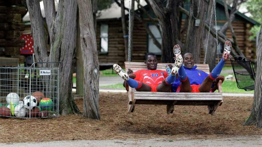 Haiti's Fritzon Jean-Baptiste, left, and teammate Paulin Jean play on a swing after a soccer training session at the T-Bar M camp in New Braunfels. The Haitian national soccer team, whose home field is being used as a temporary home for homeless Haitians, will practice in Texas for the next two to three weeks. AP Photo/Eric Gay / AP