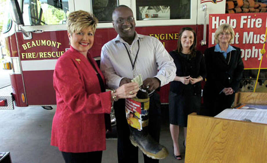 The annual Fill-the-Boot Campaign to benefit Muscular Dystrophy kicked off this morning with Mayor Becky Ames putting the first $2 into the boot held by Capt. Earl White, vice president of Local #399. Dave Ryan/The Enterprise / Beaumont