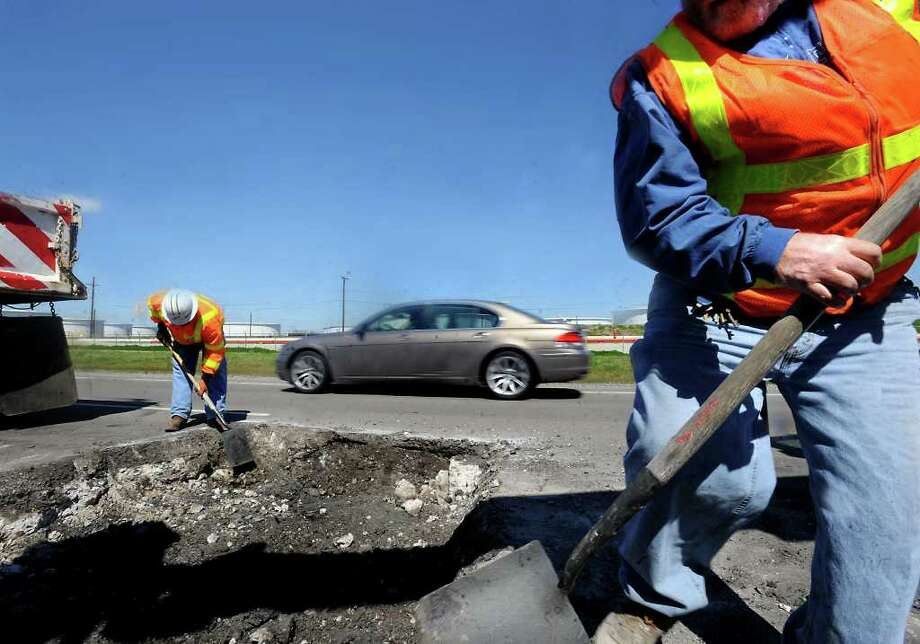 Darrel Richardson and Jon Clark dig up a portion of the asphalt as cars and trucks pass by Friday on FM 366 in Port Neches. Tammy McKinley/The Enterprise / Beaumont