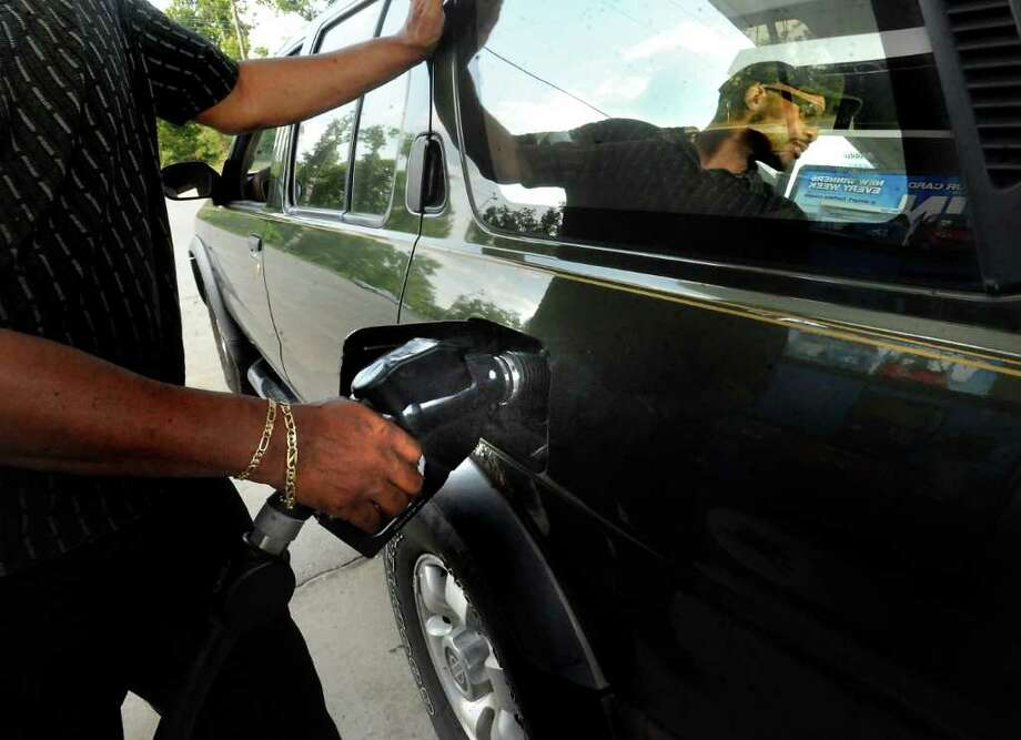 Warren Jefferson pumps gas into his SUV at the Mobil Exxpress Mart on Highway 105 Thursday in Beaumont. Tammy McKinley/The Enterprise / Beaumont