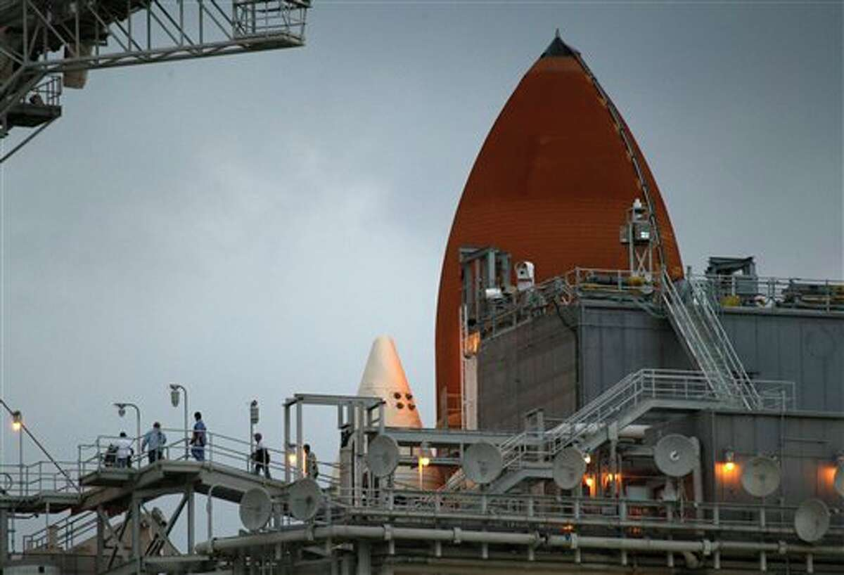NASA workers walk along a platform on the fixed service structure next to space Shuttle Discovery on pad 39A at the Kennedy Space Center in Cape Canaveral, Fla., Tuesday, Nov. 2, 2010. Discovery is scheduled to launch Wednesday. (AP Photo/John Raoux)