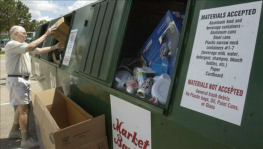 Beaumont resident John Osborne dumps a load of papers, cans and cardboard into the recycle receptacle at the Market Basket store at Phelan and 23rd street in Beaumont in June 2008.  Enterprise file photo