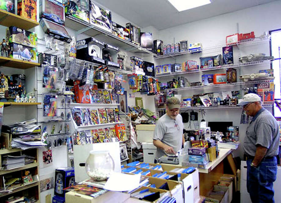 Scott Smithhart, owner of Comics Kingdom in Beaumont, rings up George Fortune of Vidor. Fortune has been collecting comic books for years and owns about 1,800, most of which he hasn't read. Instead, he puts them in protective sleeves as an investment. Dave Ryan/The Enterprise / Beaumont