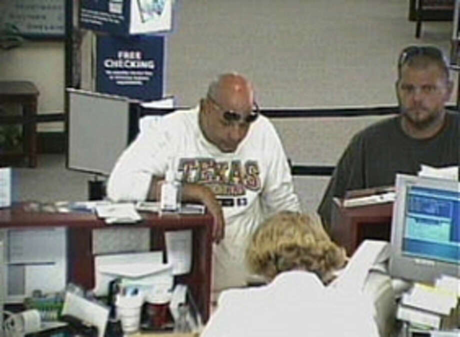 An image from surveillance video footage shows a bank customer, right, taking an iPhone left by another customer, left, Monday at Capital One Bank, 6363 Phelan Blvd.