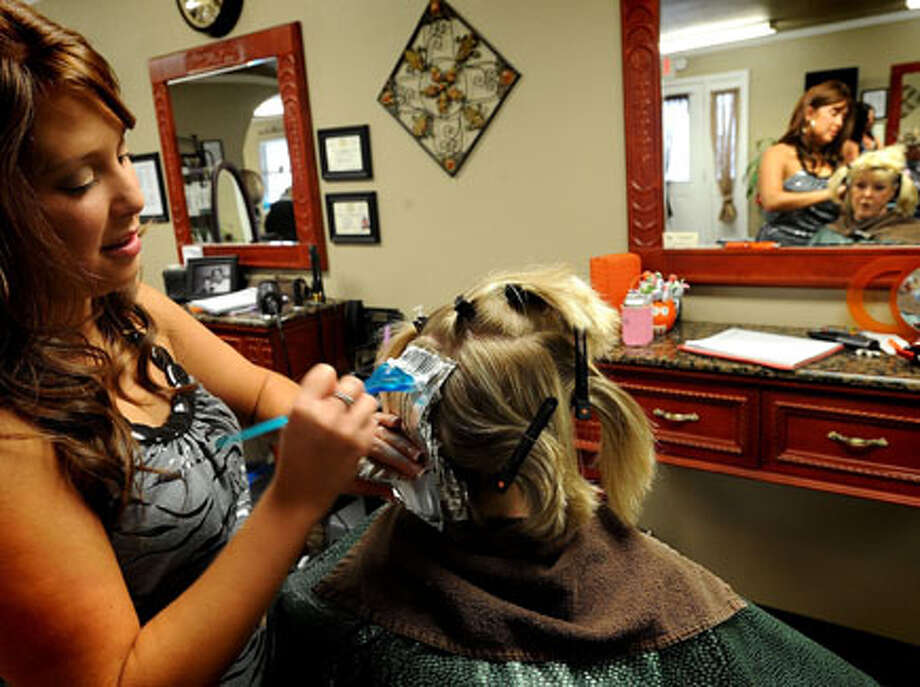 Tara Payne highlights Bernice Guidry's hair on Friday to prevent a bad hair day. Guiseppe Barranco/The Enterprise / Beaumont