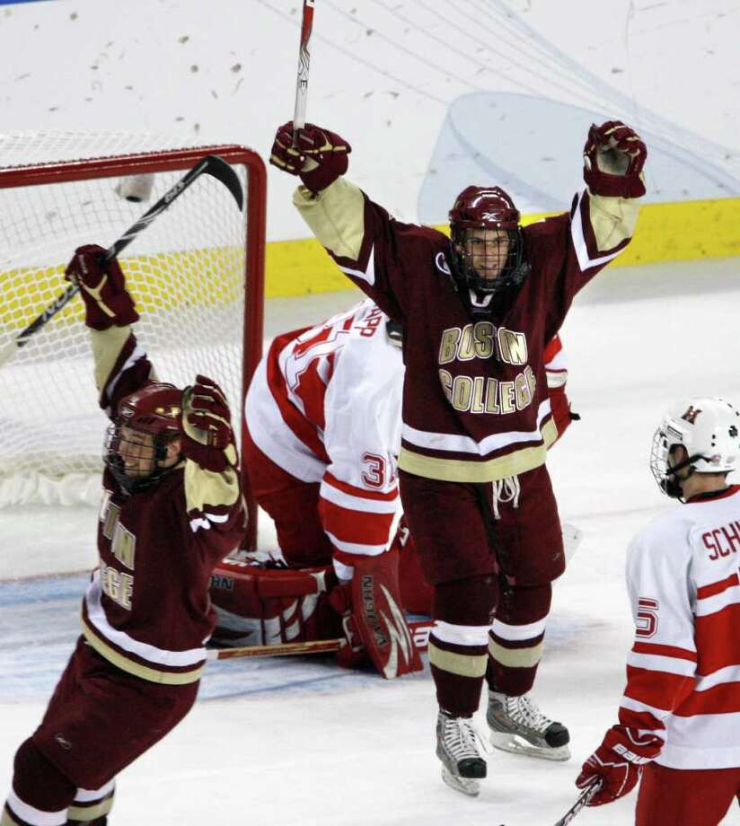 Boston College forwards Cam Atkinson, left, and Brian Gibbons celebrate a goal on Miami of Ohio goalie Connor Knapp in the first period of an NCAA Frozen Four college hockey semifinal Thursday evening in Detroit. Boston College faces off against Wisconsin in the final game Saturday night. (AP Photo/Carlos Osorio) / AP
