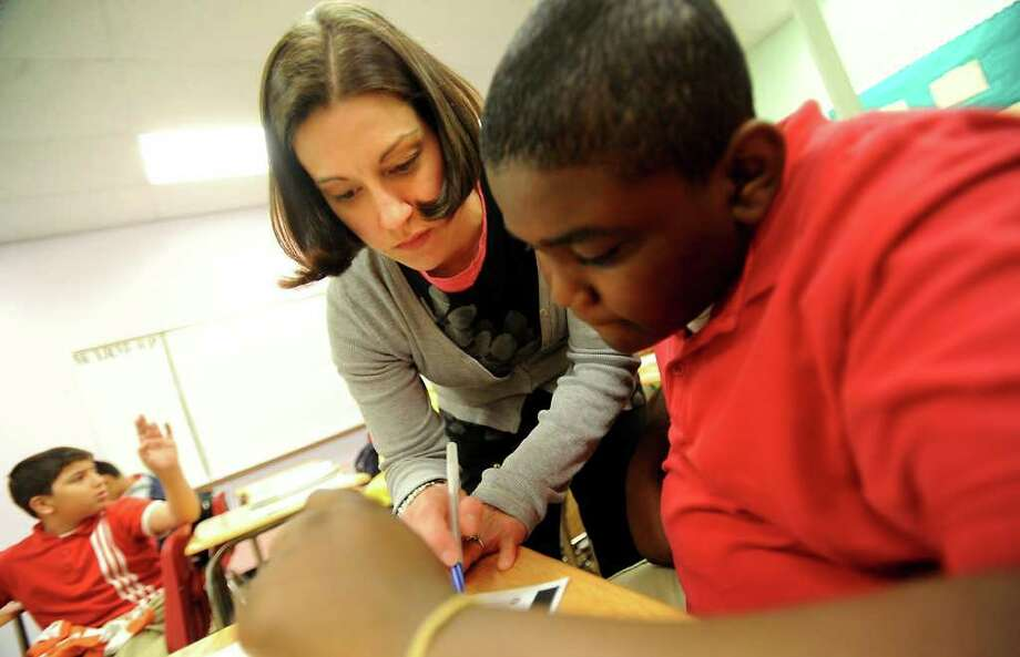 Fifth grade teacher April Harris helps Darius Sims with his math work at Harmony Science Academy Tuesday in Beaumont. Tammy McKinley/The Enterprise / Beaumont