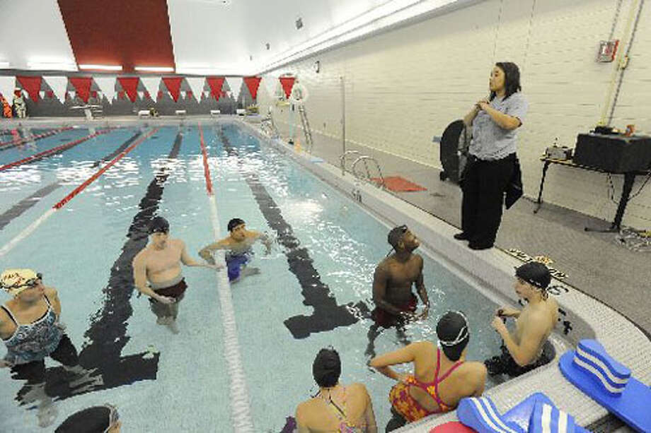 Swim coach Sheena Walker, right, works on endurance drills with swimmers from West Brook and Ozen high schools at Lamar University pool in February. Valentino Mauricio/The Enterprise