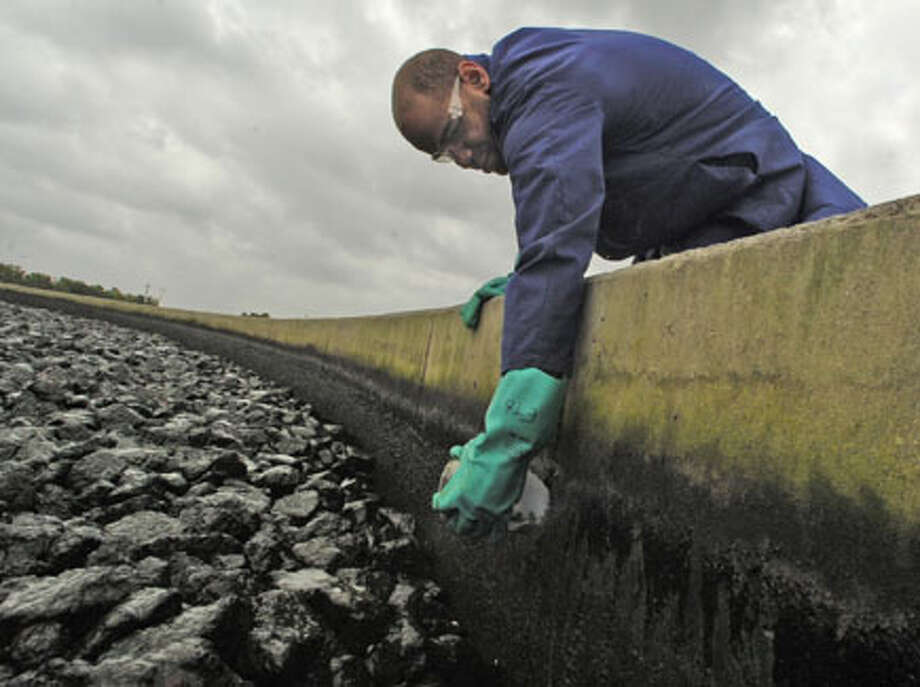 """Edward Braye III, a lab tech at Beaumont's Wastewater Treatment Plant, scrapes the side of a secondary trickling filter tank to get a sample of the """"bugs"""" that cover the rocks in the tank. The rocks, which are covered with this type of """"bug"""" that eats the bacteria, have to be checked to make sure they are alive and well routinely. Dave Ryan/The Enterprise / Beaumont"""