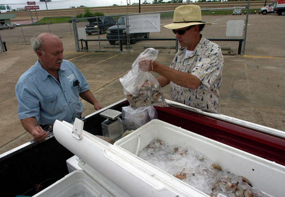Port Bolivar Seafood owner Gary Oliveira, right, weighs out a 5 lb bag of fresh shrimp out of the coolers for Howard Hassler, owner of the Trailer Hitch Depot in Beaumont.    Dave Ryan/The Enterprise
