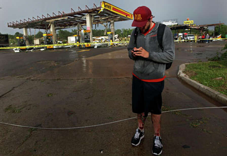 Jesse Smith has blood running down his leg as he uses his phone after a tornado caused him to crash his car at the Love's Country Store that was destroyed by the tornado Monday in Oklahoma City. AP Photo/The Oklahoman, Chris Landsberger / THE OKLAHOMAN