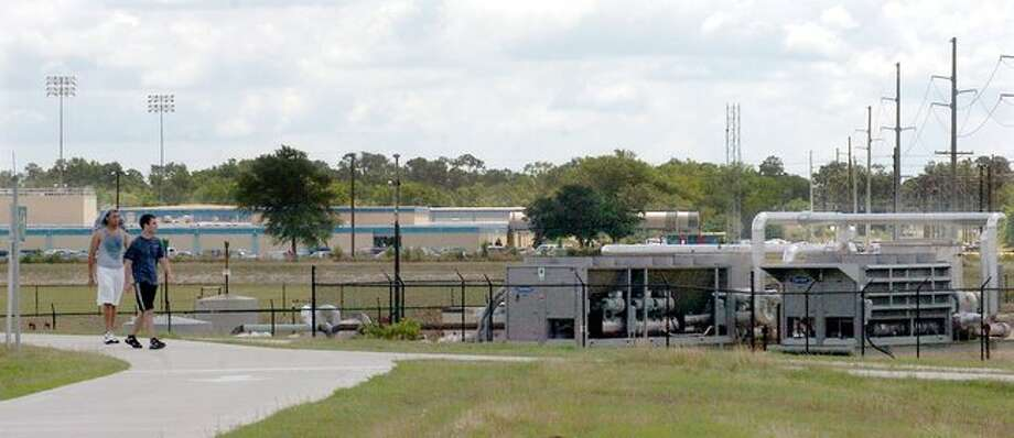 Joshua Smart,left, and Trey Billingsley walk past a natural gas production facility next door to West Brook High School in Beaumont as they leave the Gulf Terrace Hike and Bike trail after a workout Friday. Pete Churton/The Enterprise / Beaumont