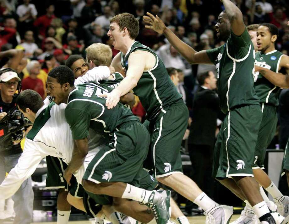 Michigan State players mob Korie Lucious after Lucious hit the game-winning three point shot against Maryland Sunday  in an NCAA second-round game in Spokane, Wash. Michigan State beat Maryland 85-83. (AP Photo/Don Ryan) / AP
