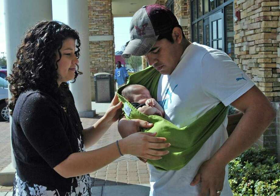 Stephanie Perez helps her husband, Miguel, put on a pouch sling to carry 3-month-old Samuel. Dave Ryan/The Enterprise / Beaumont